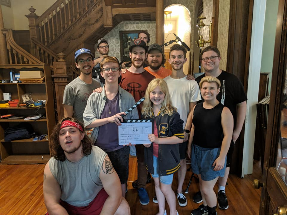 The cast and crew of 11 pose for a picture after wrap.