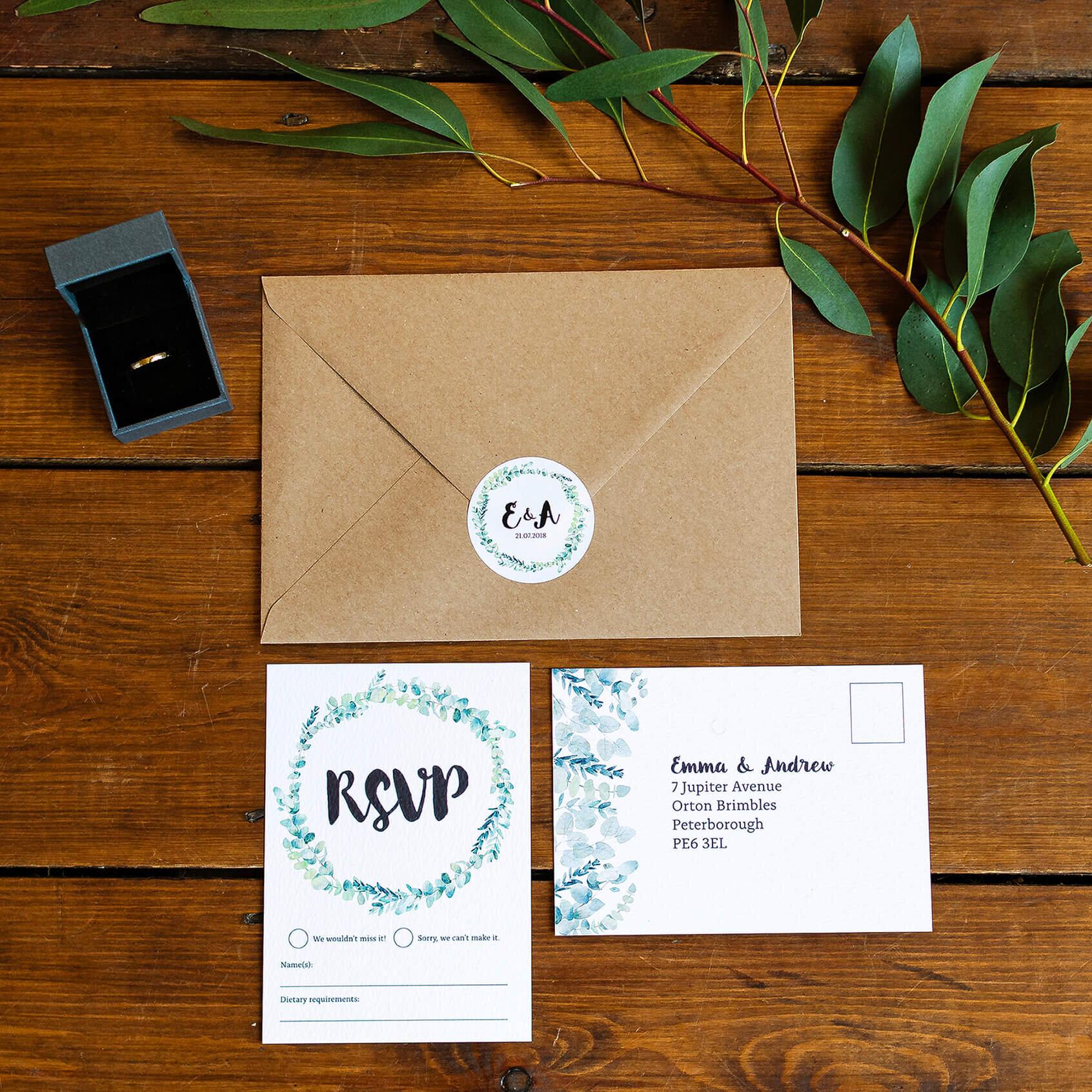 Design By Emily Rustic Eucalyptus Wedding Invitation with Kraft Brown Envelope, monogram sticker and RSVP Postcard. Molten gold wedding ring.