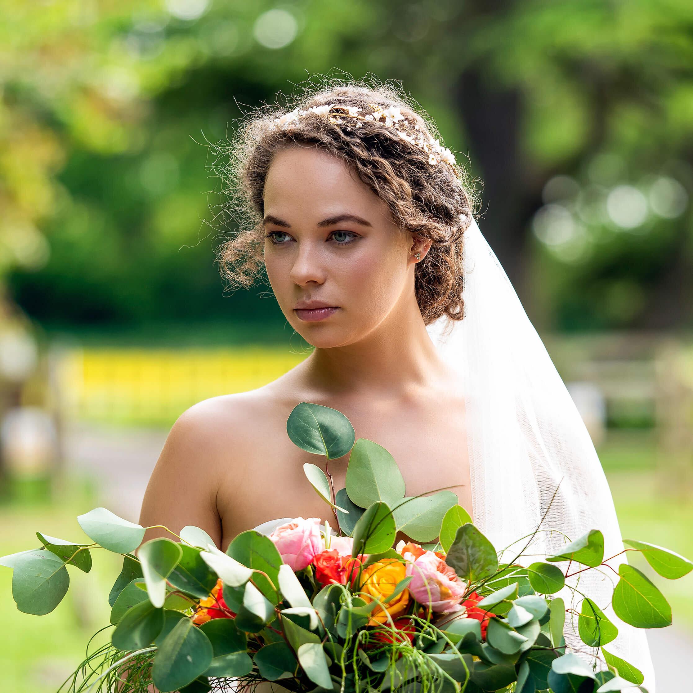 Bride with Davina Simone Weddings floral and foliage bouquet, Sash & Veil Bridal veil, and PS With Love Bridal Hair Piece, at Nurstead Court Wedding Venue, Kent.