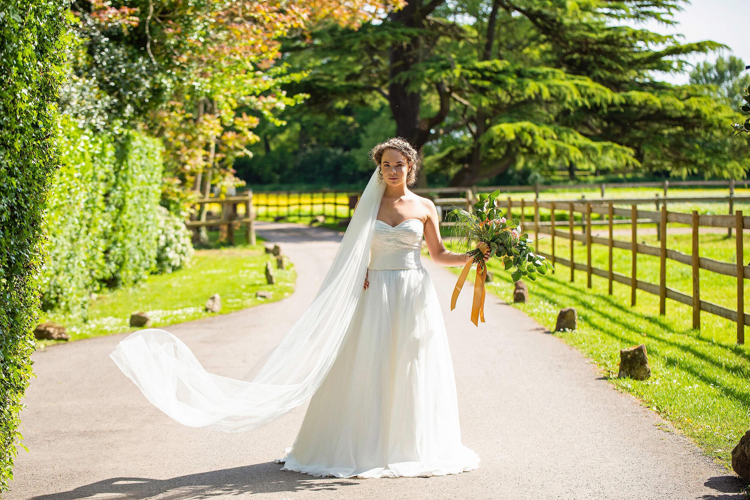 Bride in Oui Madam Bridal Atelier dress, with Davina Simone Weddings floral and foliage bouquet, Sash & Veil Bridal veil, and PS With Love Bridal Hair Piece, at Nurstead Court Wedding Venue, Kent.