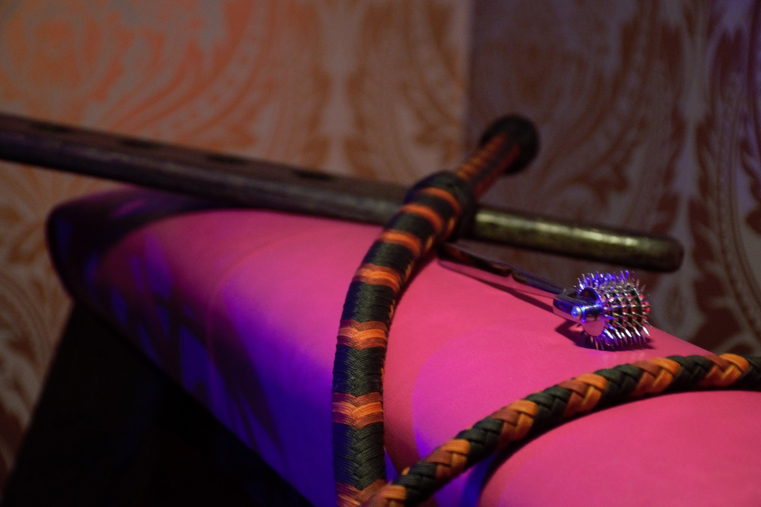A five-tiered Wartenberg wheel gleams in warm soft light, resting atop a hot pink spanking bench next to a long nylon whip and dark wood paddle