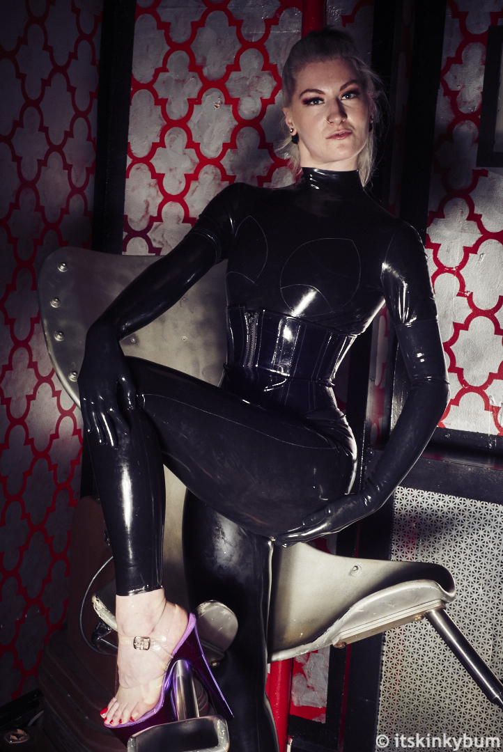 Miss Adah, clad entirely in black latex—catsuit, gloves, corset—presents her foot for you to kiss © itskinkybum.jpg