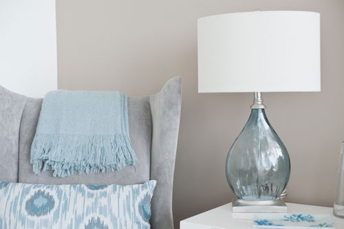 gray-wingback-chair-blue-glass-lamp-throw-and-decorative-pillows.jpg