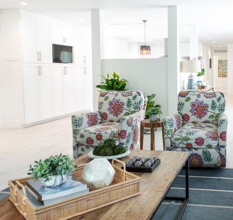 living-room-blue-rug-modern-farmouse-design-floral-swivel-armchair-gray-leather-sofa-decorative-pillow-geometric-curtains-cropped.jpg