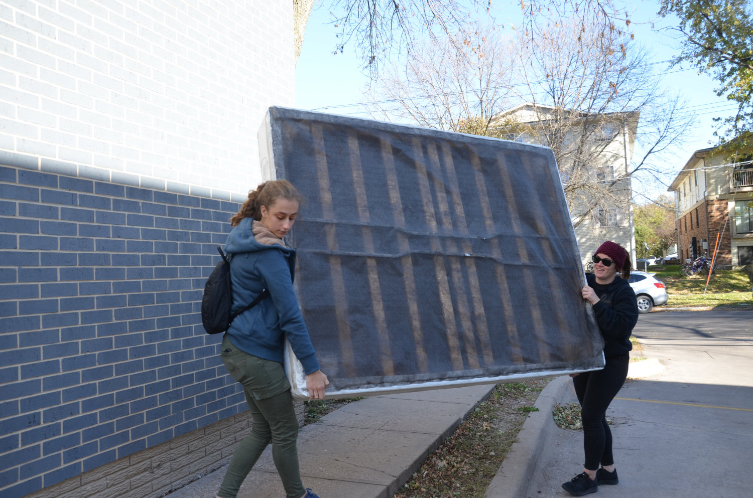 Volunteers carry a boxspring into a downtown Iowa City apartment.