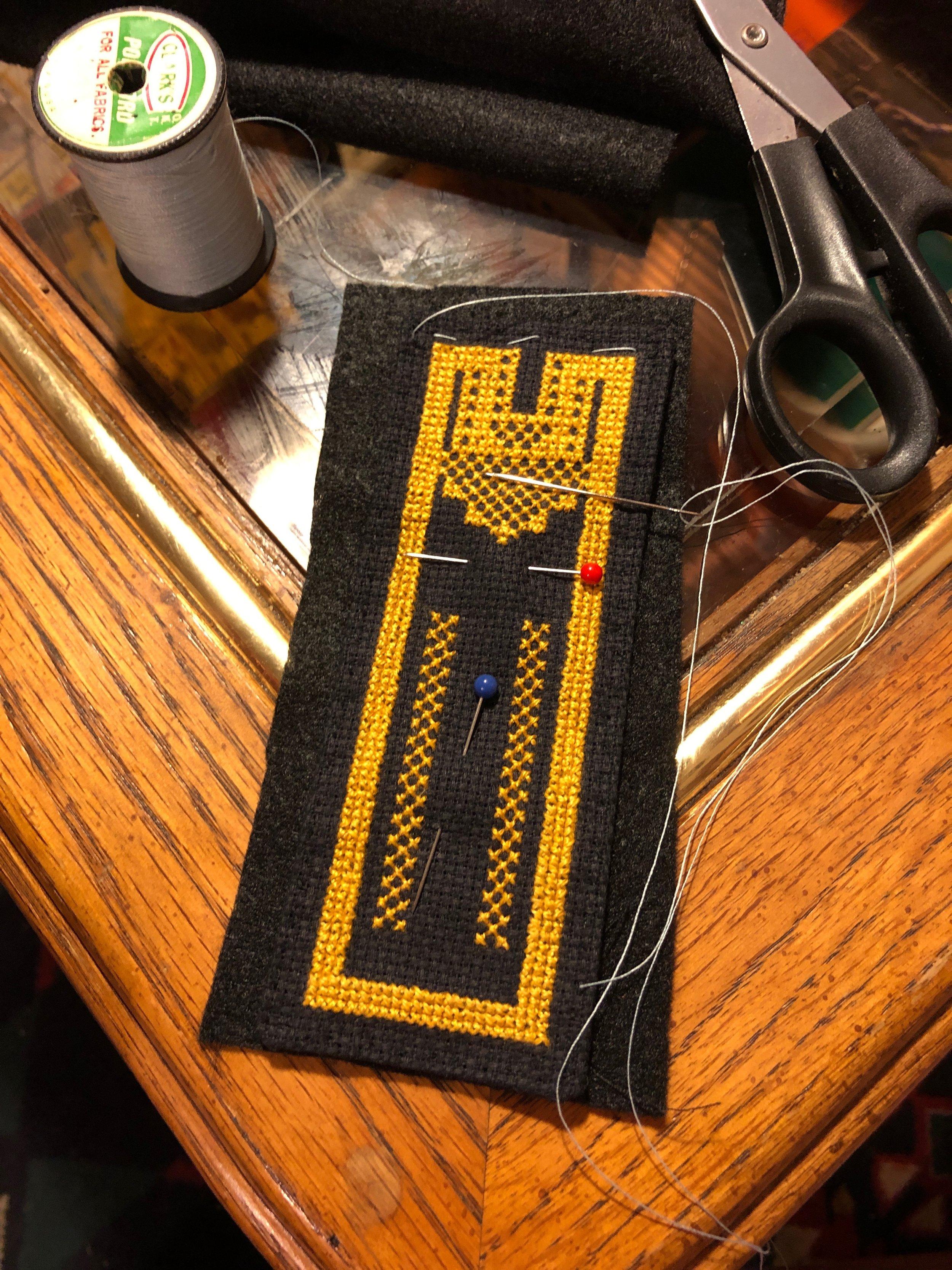 """Basting"" the uncut felt onto the Black aida cloth with white thread"