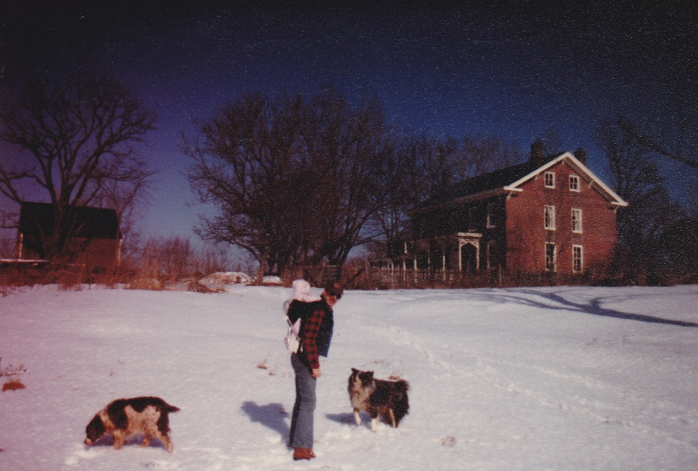 Kris, carrying a one year old Lia, with dogs Girlie and Bronco, winter 1983. The house in the background with its new roof.