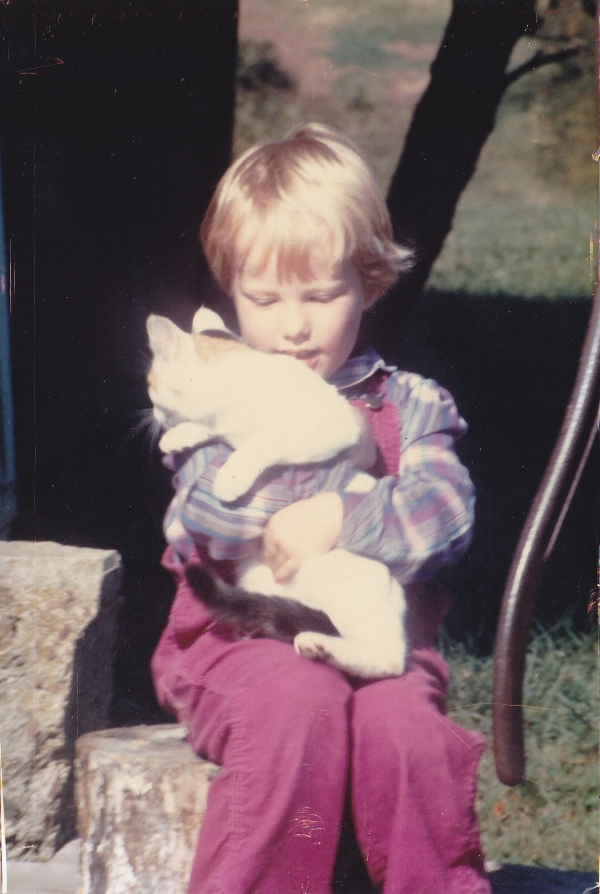 A young Lia, with one of the numerous barn cats.