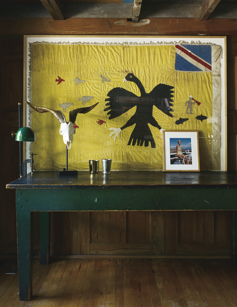 in the living room, a vintage flag from Ghana hangs over a wooden console table. The walls are paneled in wooden doors salvaged from a shipwreck.
