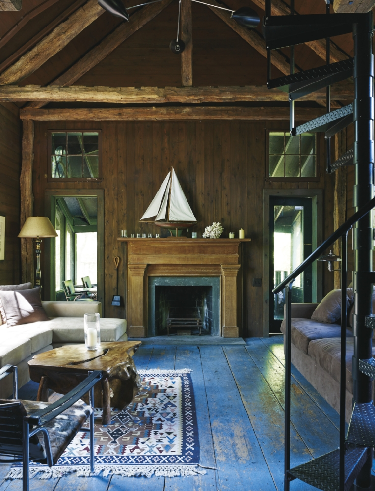 The living room of the guesthouse, which began as a storage barn adjacent to the main house. It was originally reimagined by Bruce Weber 's friend and set designer, John Ryman, with a loft bedroom and screened-in porch.