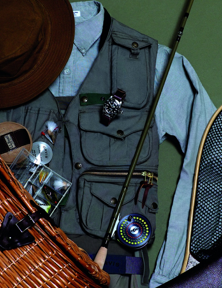 Guide vest and original hat FILSON, button-down shirt ENGINEERED GARMENTS, silver sonic convertible top waders, landing net, superfine glass fly rod, fly wallet, and cfo reel ORVIS, classic trout knife, fly box, and wicker creel L.L.BEAN  red submariner watch ROLEX available at manoftheworld.com