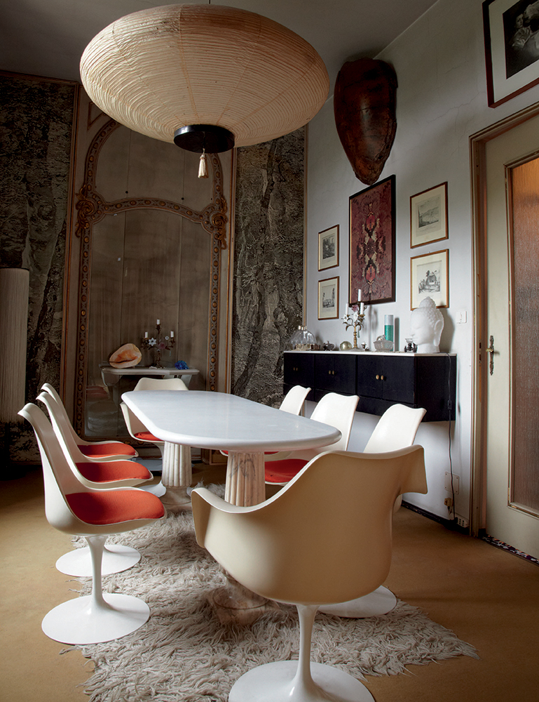 In the dining area, a bouquet of Saarinen tulip chairs surrounds a Mollino-designed marble table. A fringed lamp by Mollino's friend Gianfranco Frattini peeks out from the corner (top left). The black cabinet conceals a bar.