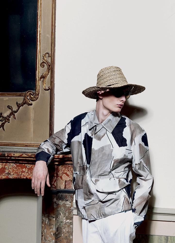Slate coated canvas blouson, cotton shirt, and linen one-pleat trousers HERMÈS sunglasses PERSOL