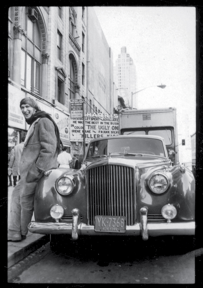 Posing with his Bentley in Times Square, New York City, 1960s. Photograph by Jay J. Good.