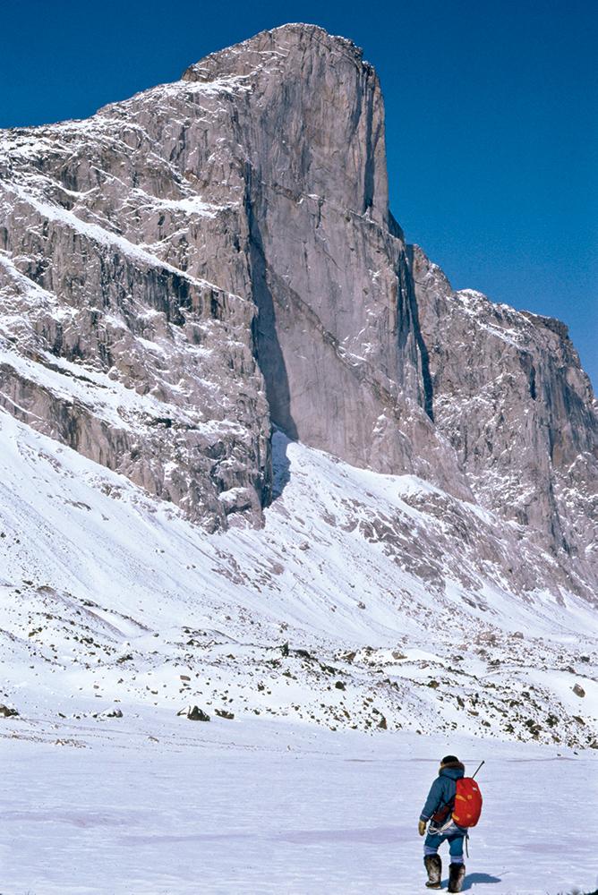 Inuit Tommy Killabuck waking beneath 4,000 foot high Mount Thor, Baffin Island, Canadian Arctic.
