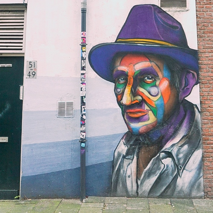 Rotterdam Street Art. Man with purple hat and face painted in many colours including red, yellow green and purple. Witte de WIthstraat.