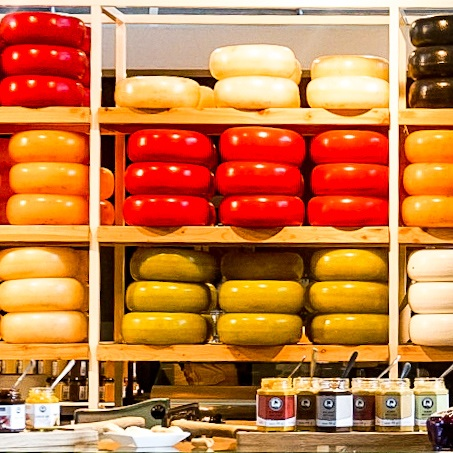 Colourful Dutch Cheese Rounds in red, yellow, white and green on shelves. The in front of shelf has cheese tasters and chutneys for customers