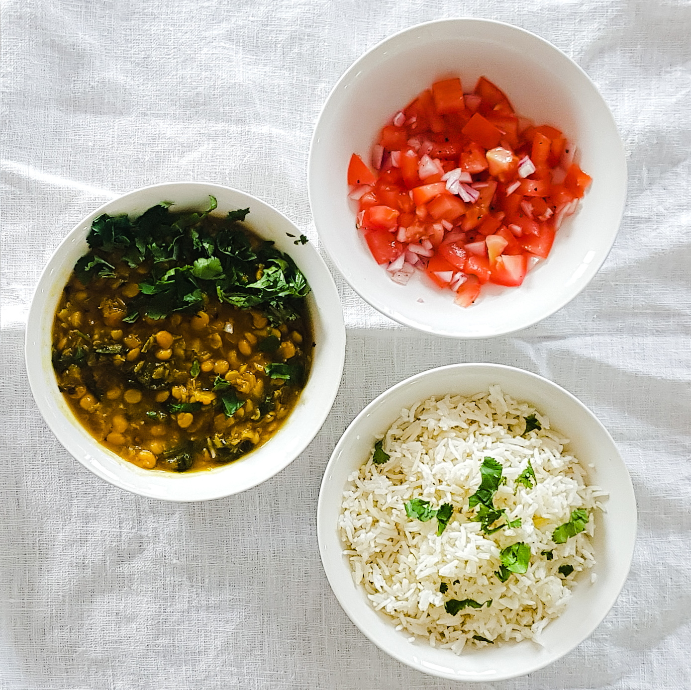 Three white bowls on a white linen table cloth in a triangle. The first bowl is filled with dahl. The second wiht cooked rice, topped with coriander and the third is filled with a tomato and onion salad!