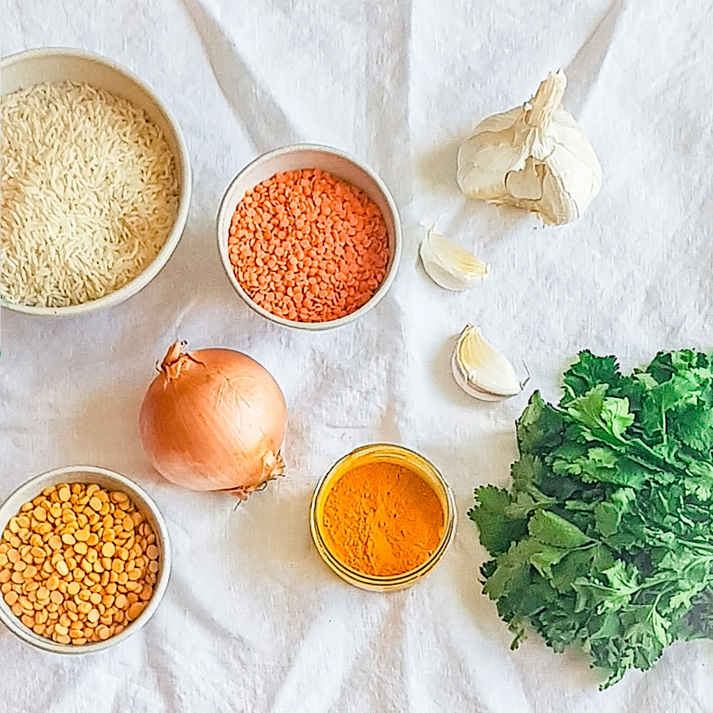Ingredients for dal on a white linen table cloth. Red lentils, chana dal, an onion, garlic bulb, bunch of freshc coriander and turmeric in a glass bowl.