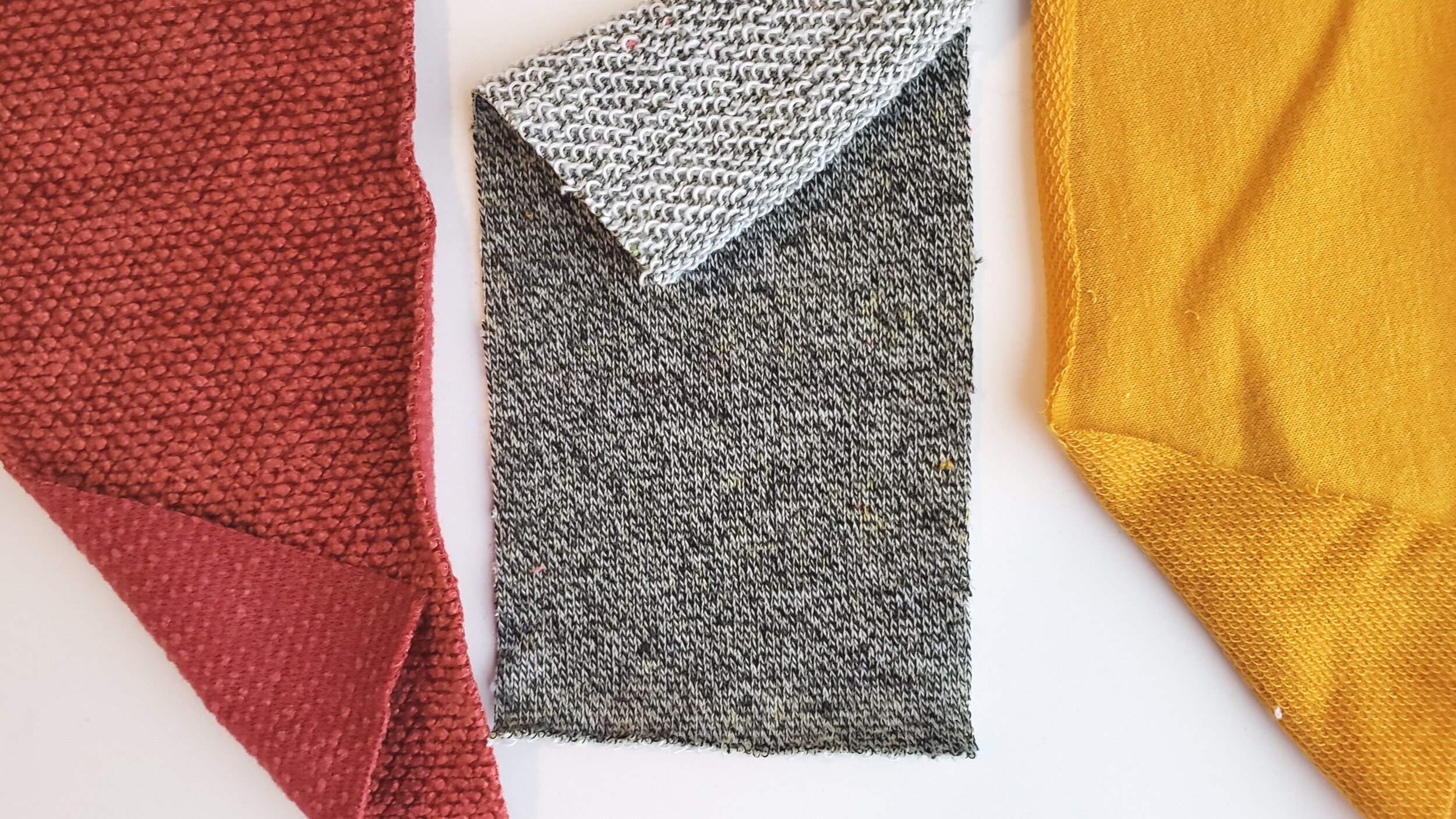 Left to right: red chenille sweater knit, grey french terry, and yellow baby french terry