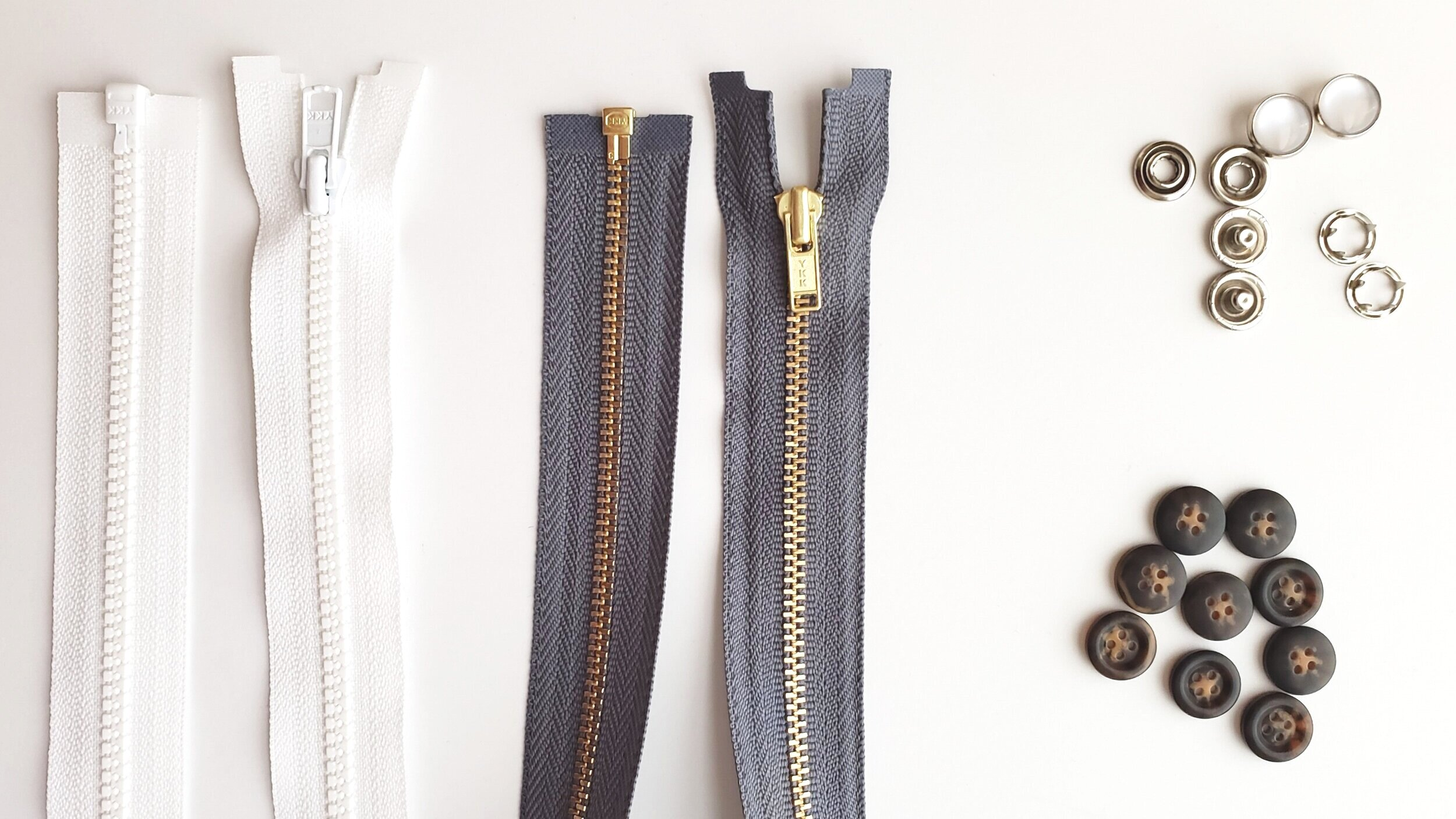 Left to right: #3 molded plastic separating jacket zipper, #3 brass separating jacket zipper, pearl snaps (top), and plastic buttons (bottom)