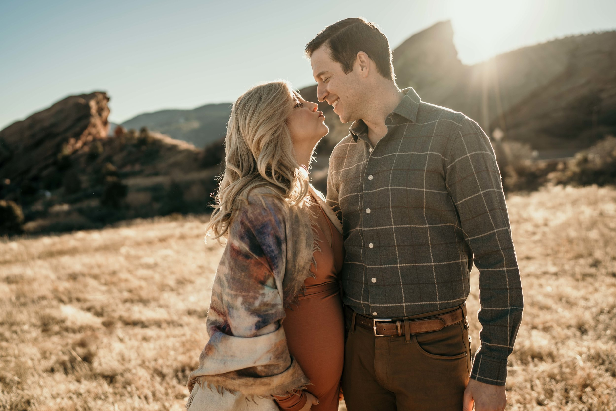 denver  maternity photos at red rocks kissing in the sun