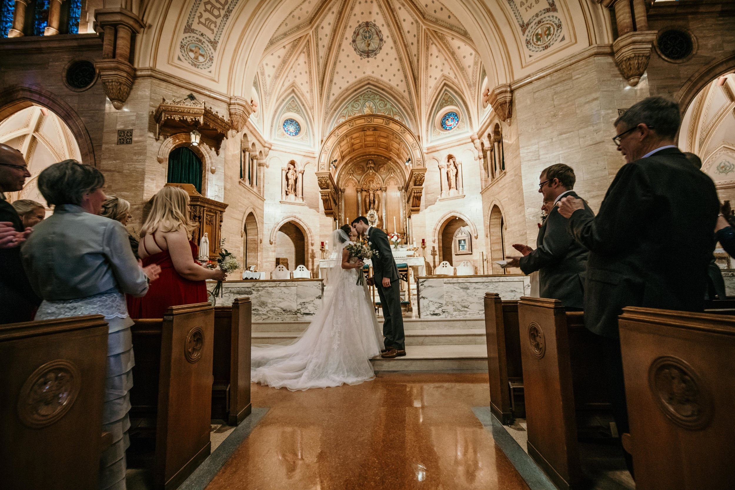 denver wedding at holy ghost church first kiss