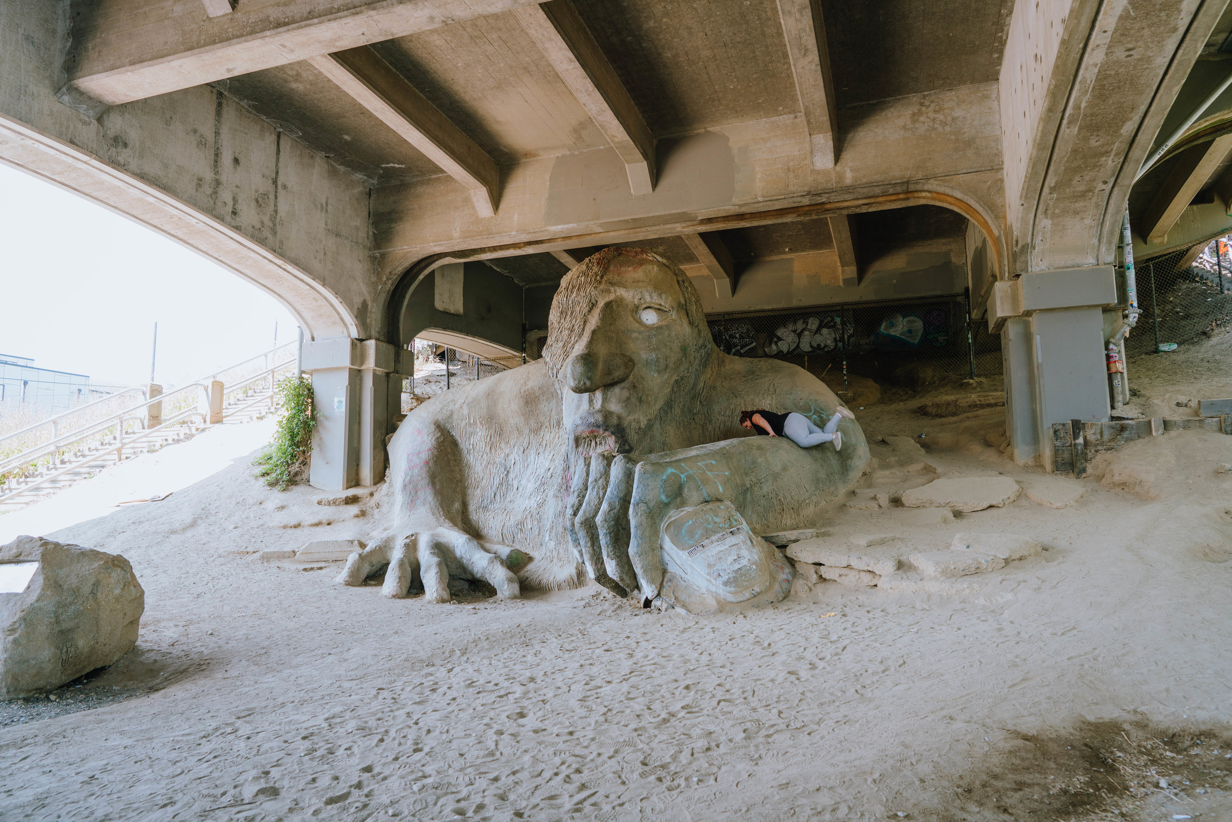 A tourist mantling the Fremont Troll in the Fremont neighborhood of Seattle, WA.
