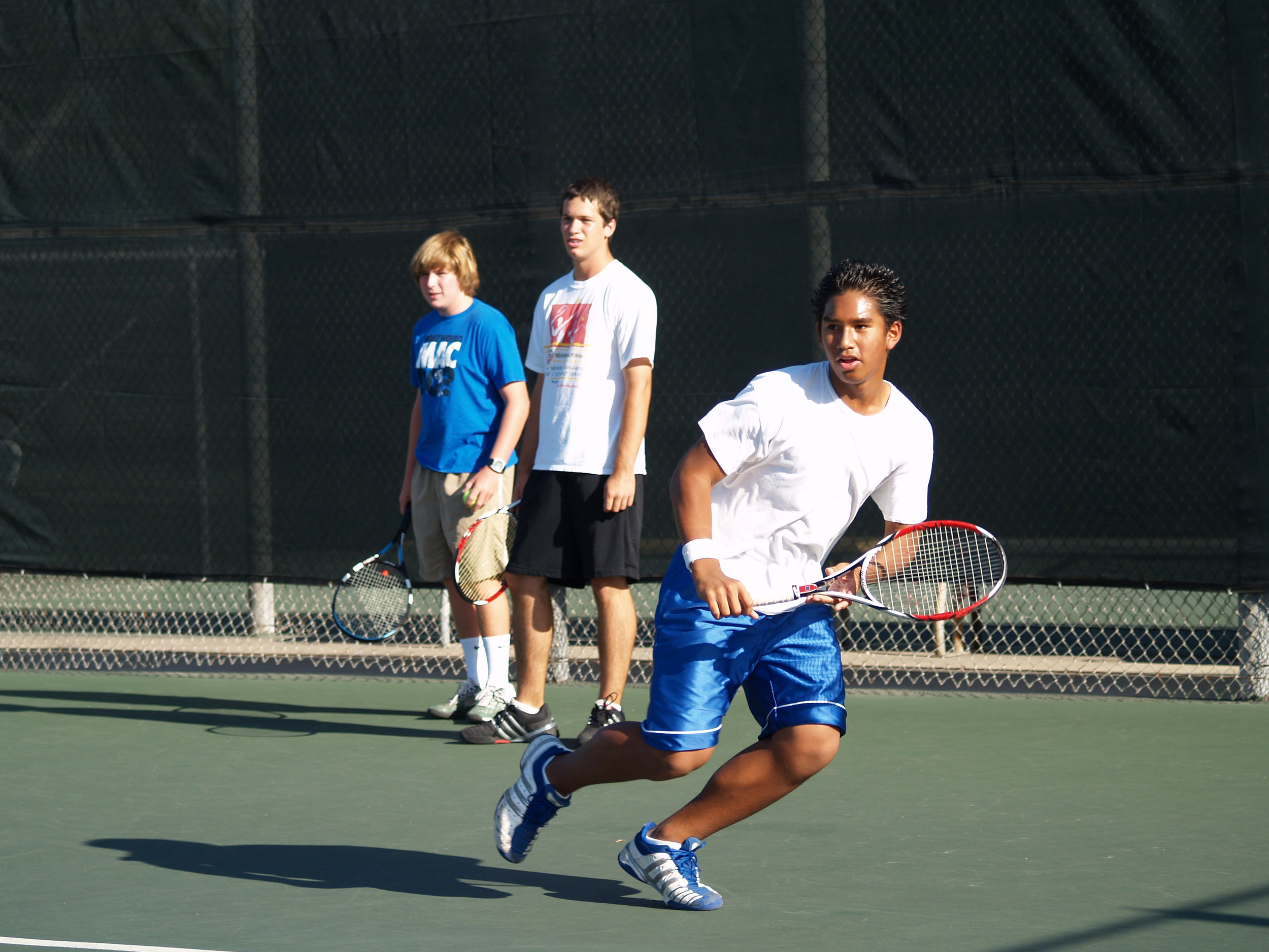 Running to catch the ball for a one-handed backhand.