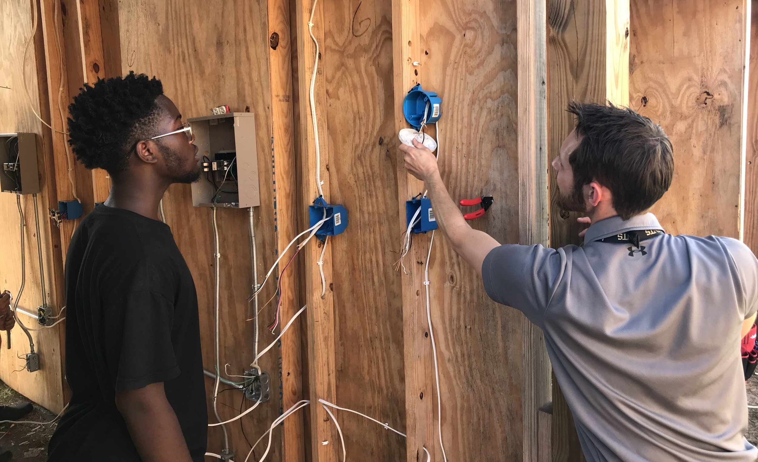 Adam Bourne stops to show a student in NOTEP's summer program the correct way to install a fixture.