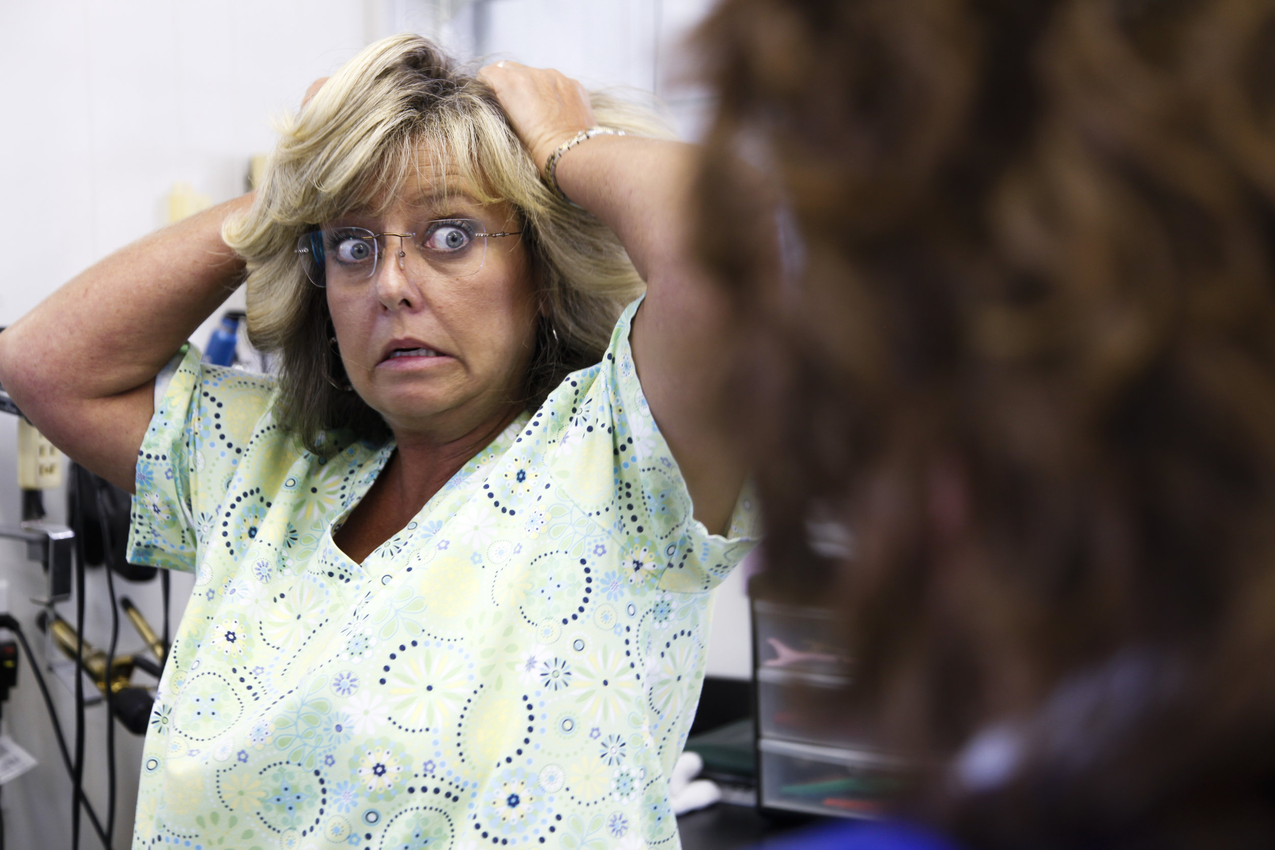 Kelly Alvey (left) talks to her friend Rhonda Gillham about how frizzy her hair gets at the salon.