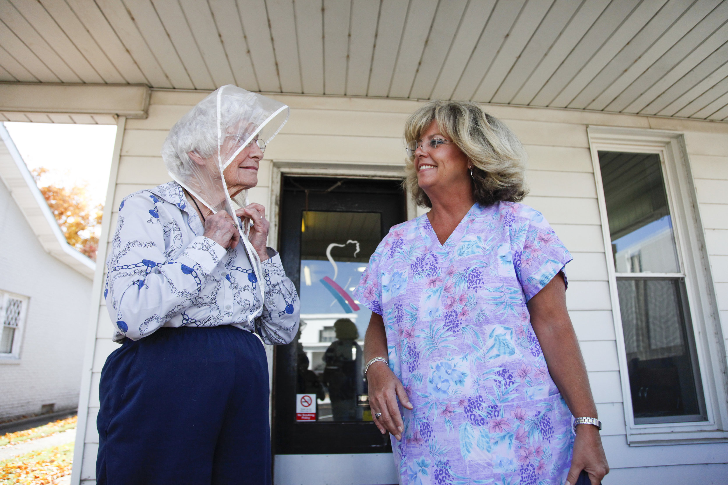 Kelly Alvey, (right), holds Gladys Luck's purse as she puts her rain scarf on after receiving her weekly hairdo at Kelly's Mane Event. Because 90-year-old Gladys has walking difficulties, Kelly assists her when she leaves the salon.