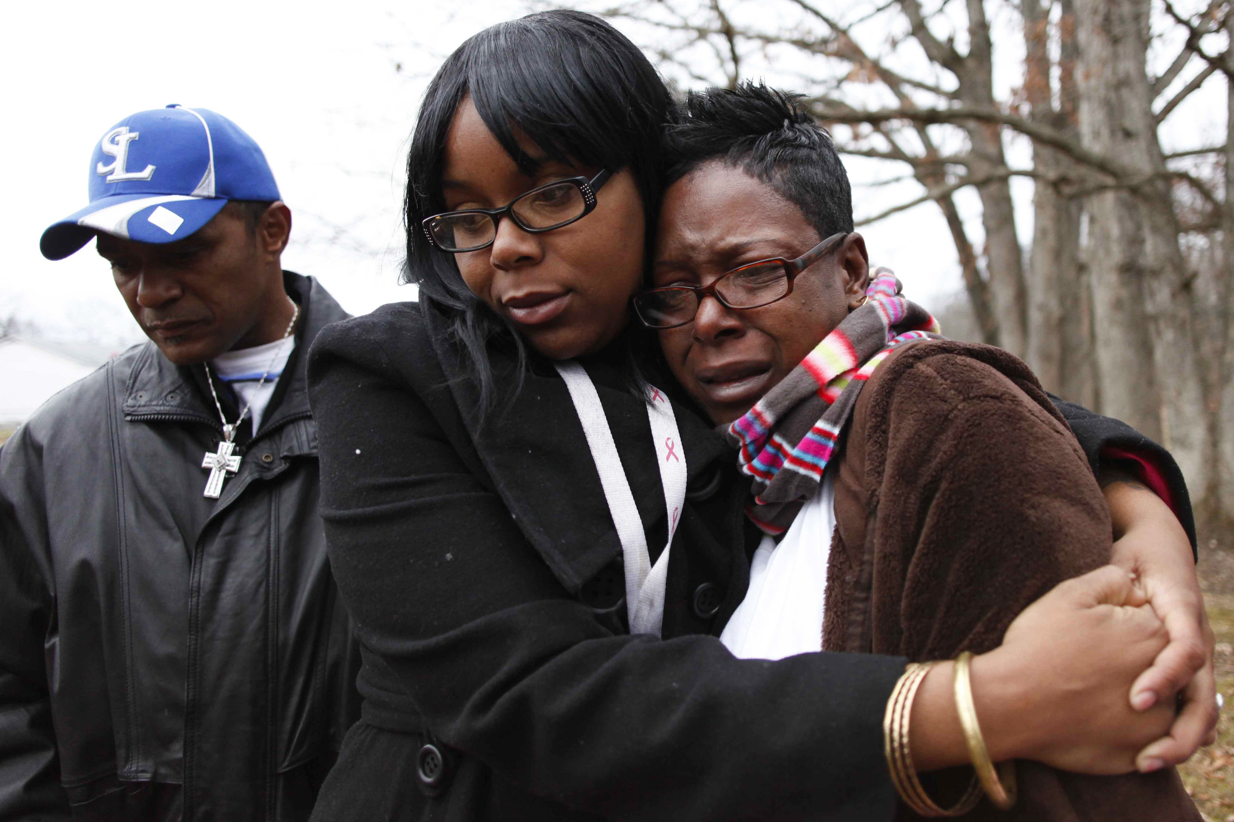 Taquaisha Nelson, center, hugs her mother Trinia Nelson, right, as they visit the grave of brother and son, Tevin Nelson, Monday, Dec. 26, 2011 at Log Providence Cemetery. Tevin's father, Keith Holmes, left, looks on his son's grave as well.