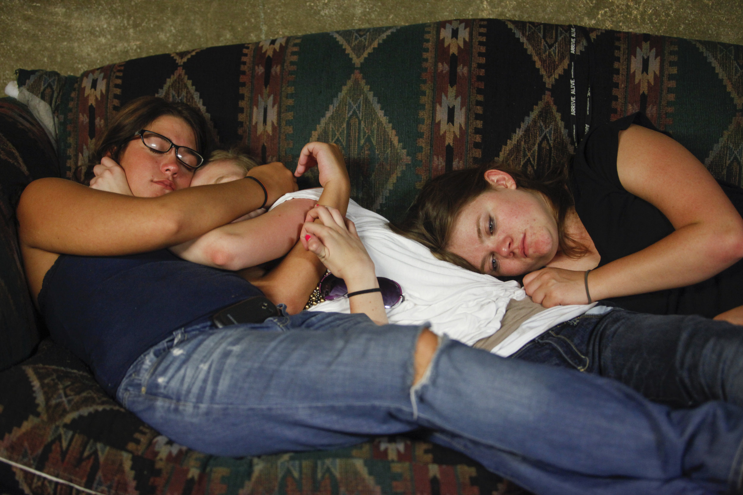 Cami Barnita, left, hugs Heather Hopkins as they are about to pass out after a party on the couch of their friend Sunday evening, May 6, 2012 in West Plains, Mo. Samantha Price lays with them and looks away.