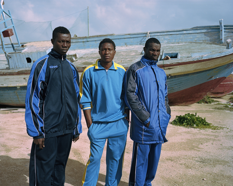 """Somaro, 19, Bouba, 19, and Abdoul, 22, arrived on the island of Lampedusa one week prior to this image being taken. They experienced a particularly rough journey and all expressed their trauma of what was faced at sea. Usually vessels leave Libya in the """"peak season"""" between May and September when seas are calmer, but in this case the traffickers forced them to take the journey. They had little information regarding their situation in Lampedusa and did not know when they would be transferred to mainland Italy."""