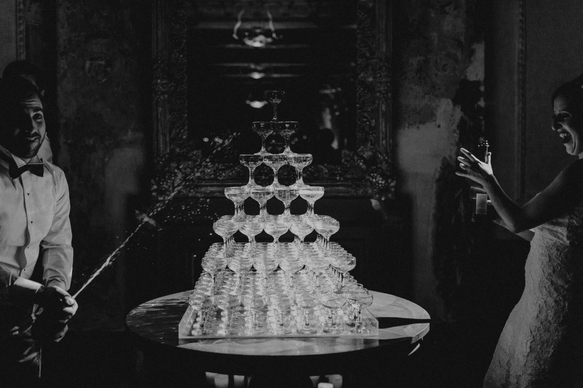 A recently married couple celebrating their wedding by pouring a champagne tower. The George Ballroom - Melbourne