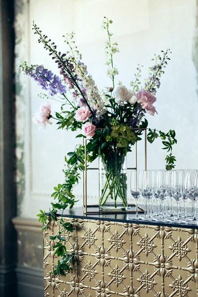 A floral arrangement on a copper bar.