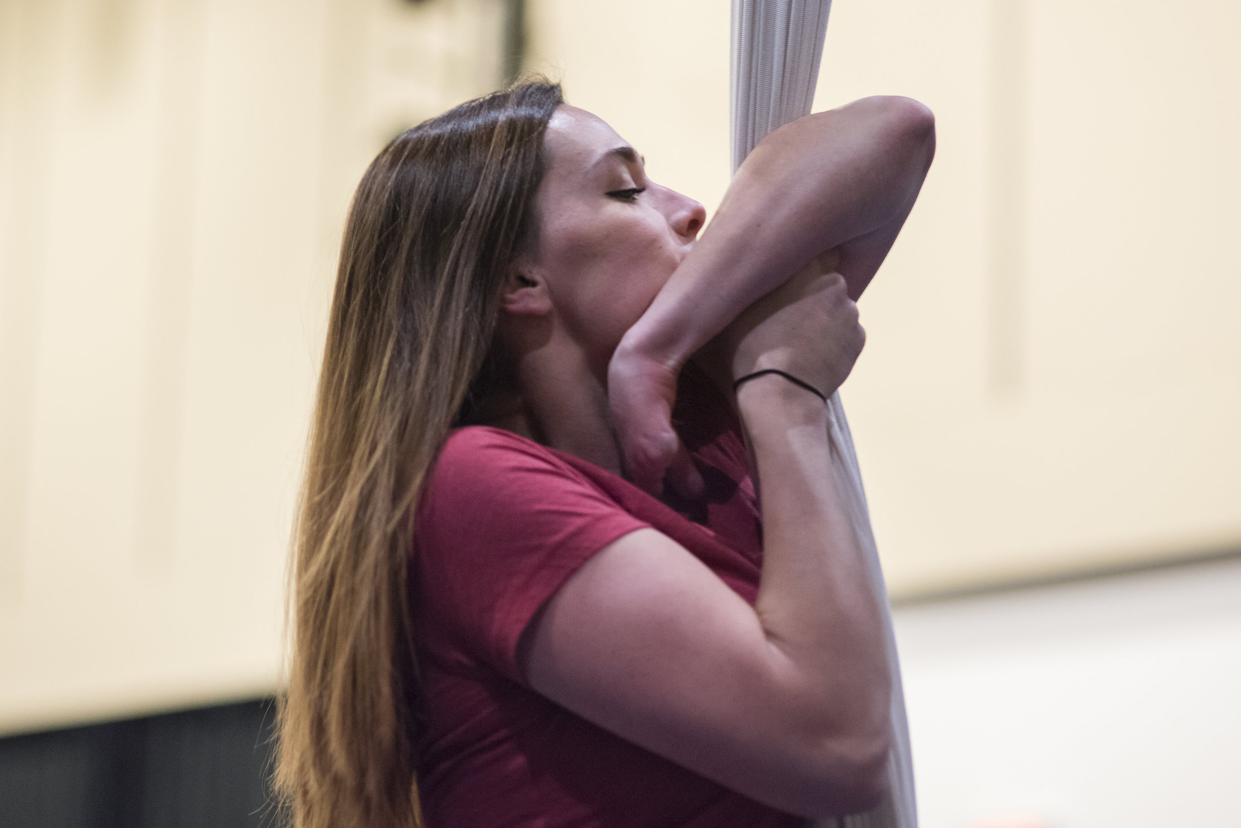 Sarah Tuberty, a graduate student in Boston University's Sargent College, climbs the fabric during a weekly aerial dance class held at BU. Tuberty was born with Symbrachydactyly, a congenital abnormality leaving her with no fingers on her left hand other than a semi-operable thumb.