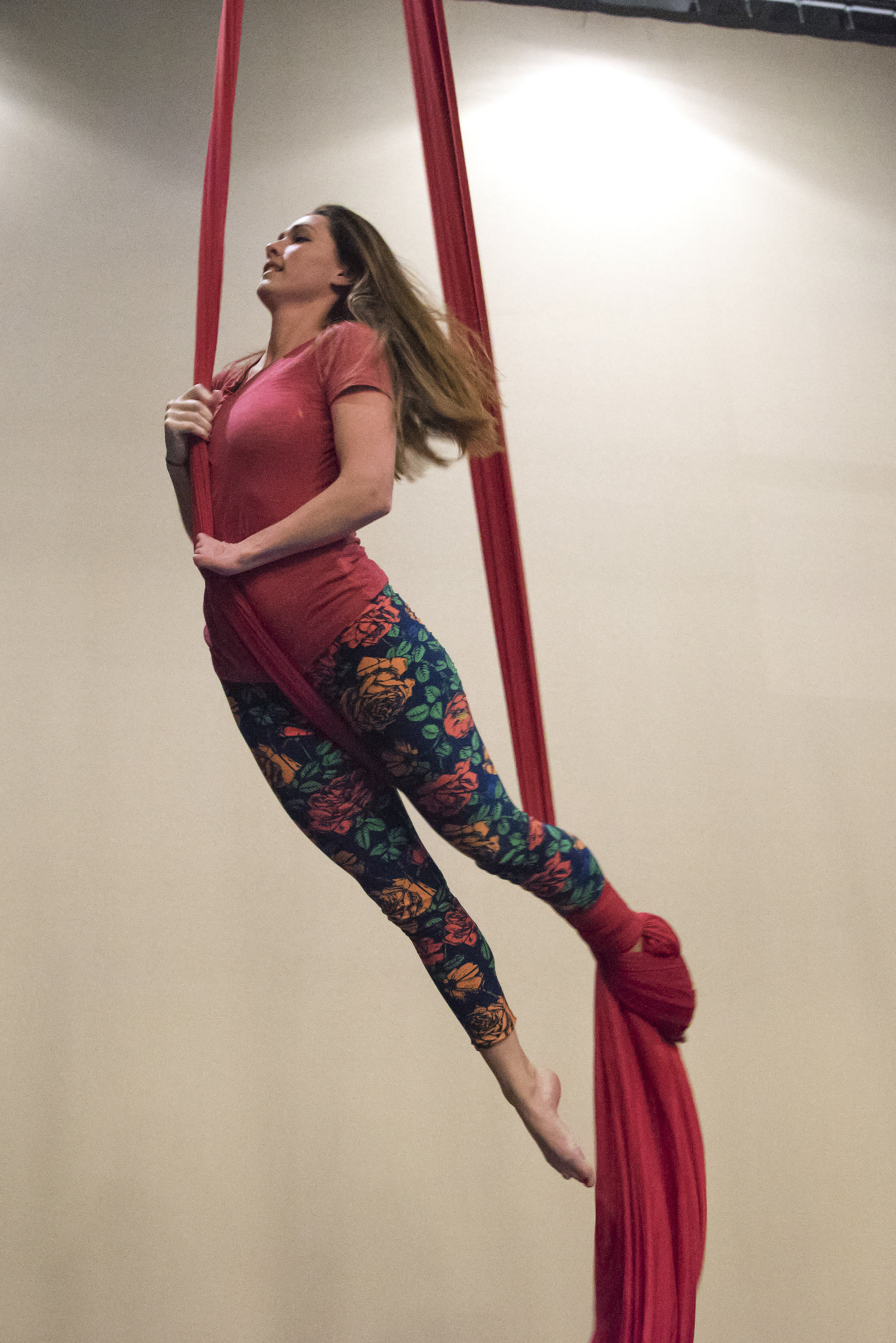 Suspended three feet in the air, Tuberty performs a peppermint wrap, one of the first silks moves students learn in a beginner aerial class. Tuberty must find new and different ways to approach aerial moves in order to accommodate the limited use of her left hand.