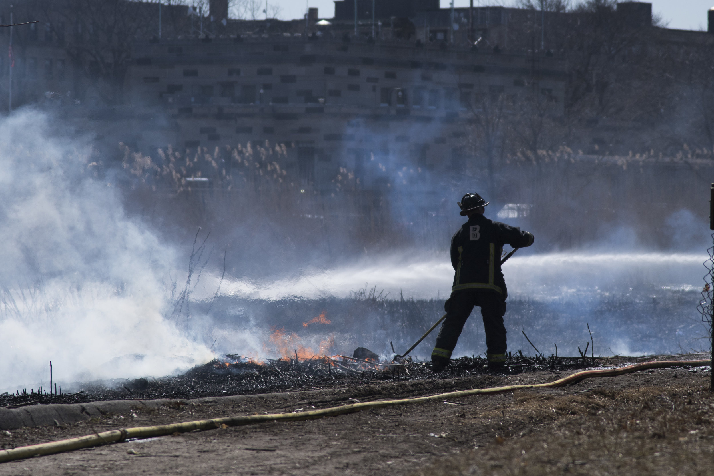 "Firefighters put out the last embers of a brush fire in the Back Bay Fens March 28, 2019. Although officials were not sure what exactly started the blaze, the dryness of the park's plant life was a contributing factor. Fires such as these are relatively common: ""this kind of thing happens almost every year,"" said a police man on the scene."