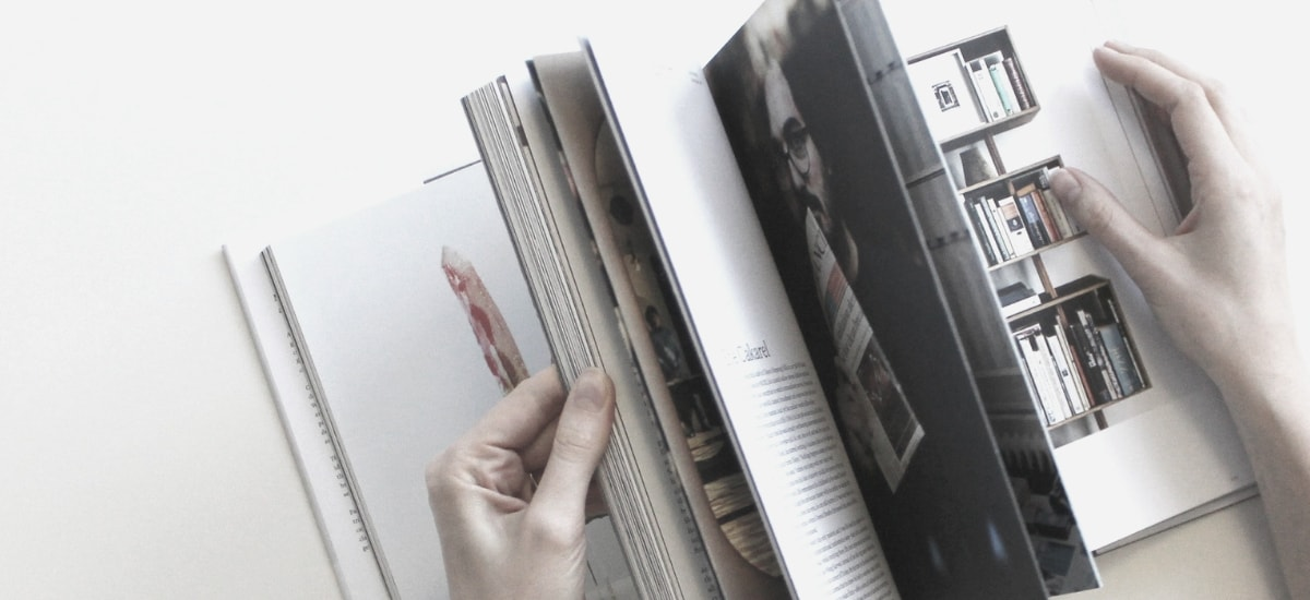 Woman flipping through content in a print magazine.