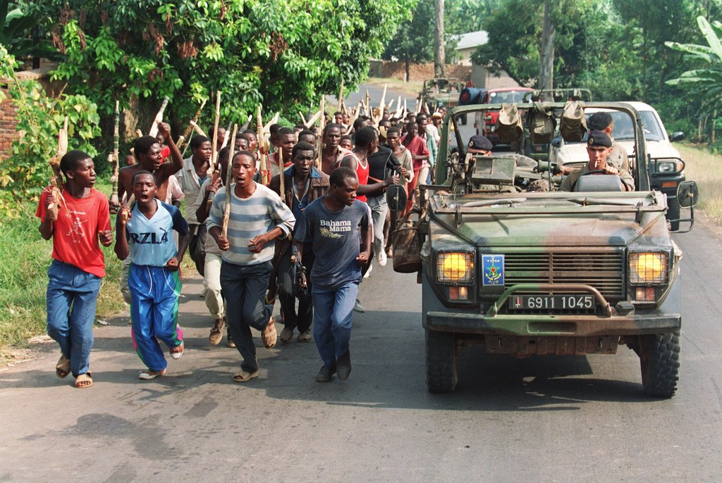 French soldiers patrolling past Hutu troops from the Rwandan government forces in 1994. Photo credit: Pascal Guyot/Agence France Presse — Getty Images.