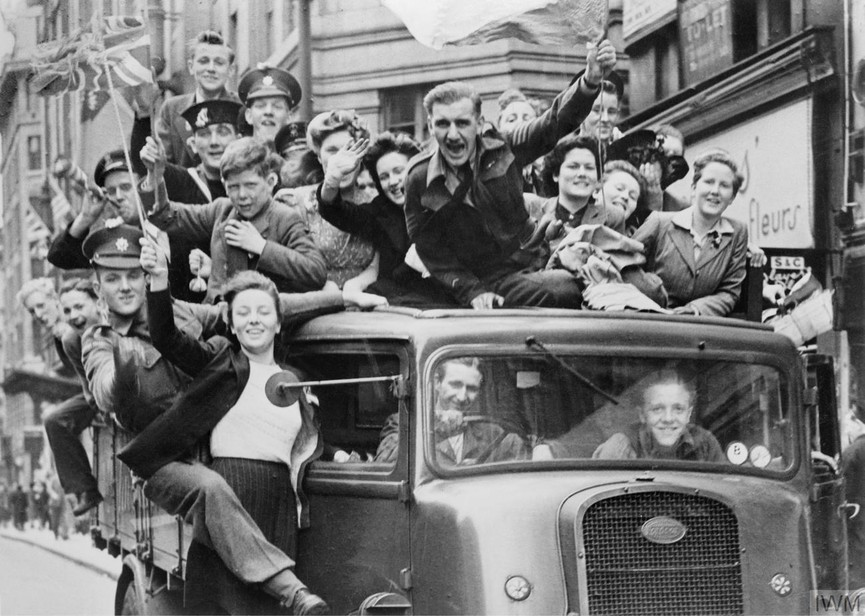 Revellers ride a truck along the Strand in London. Photo credit:  © IWM (HU 41808)  Photo soure:  https://www.iwm.org.uk/history/10-photos-of-ve-day-celebrations