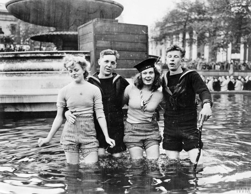 Two British sailors and their girlfriends wading in the fountains in Trafalgar Square on VE Day. Photo credit: © IWM (EA 65799)  Photo source:  https://www.iwm.org.uk/history/10-photos-of-ve-day-celebrations