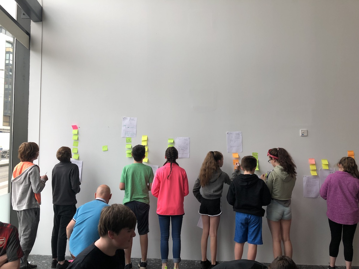 Young people working through their ideas together on post-its.