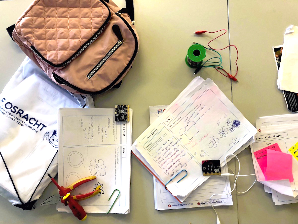 A selection a design and learning materials which the young people are provided with during the camp. Included is : Fiosracht designed  'Learning Log' , Fiosracht notepad and pen, Fiosracht bag, BBC micro-bit and tools.