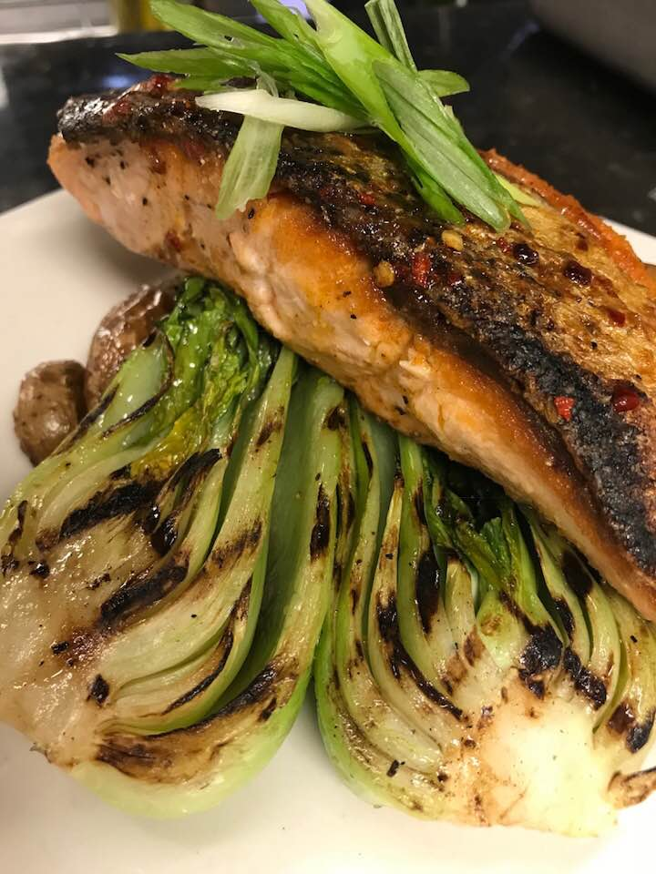 Crispy skin salmon with a spicy Korean chili butter over grilled bok choy