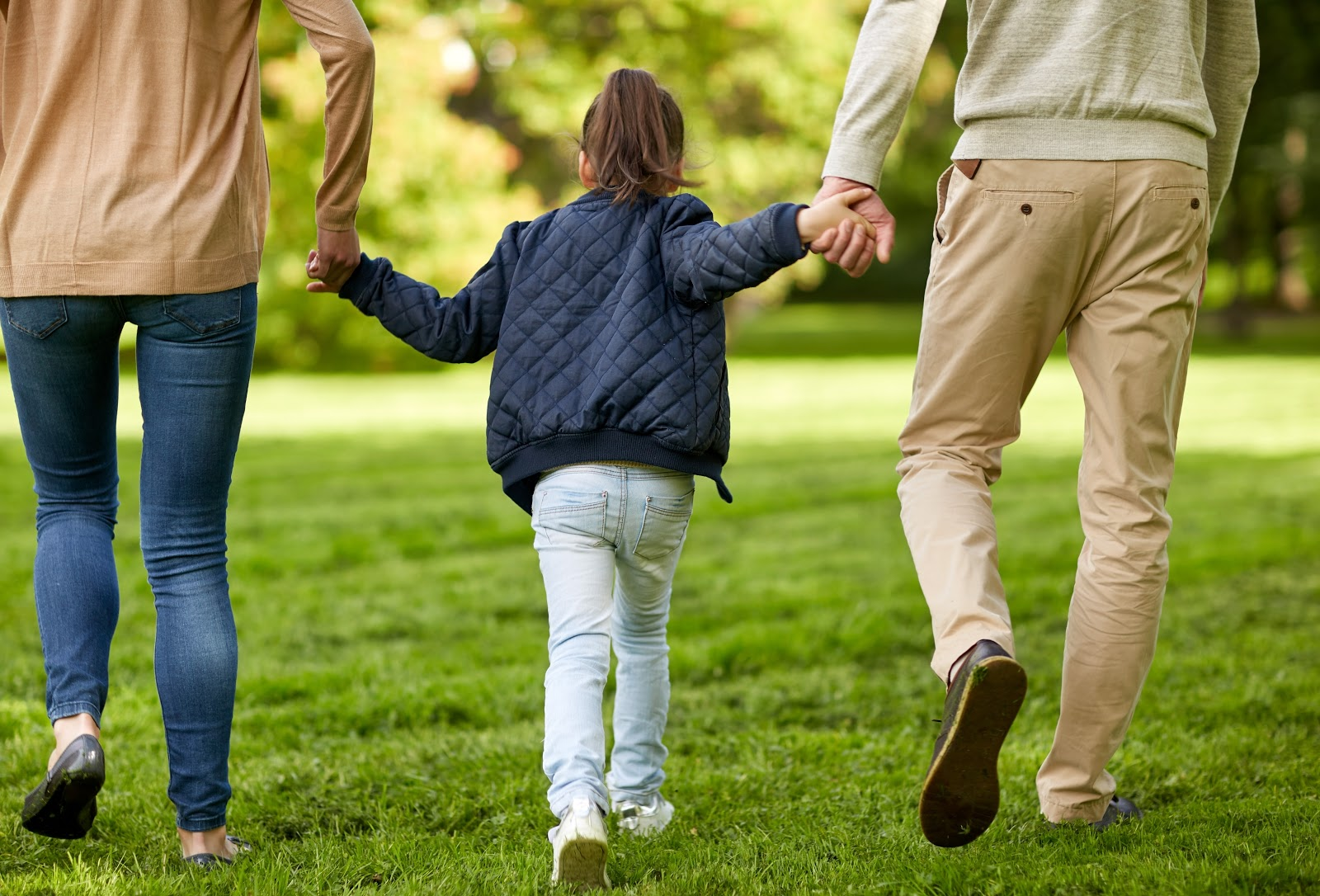 Little girl with one hand held by each parent walking through the grass