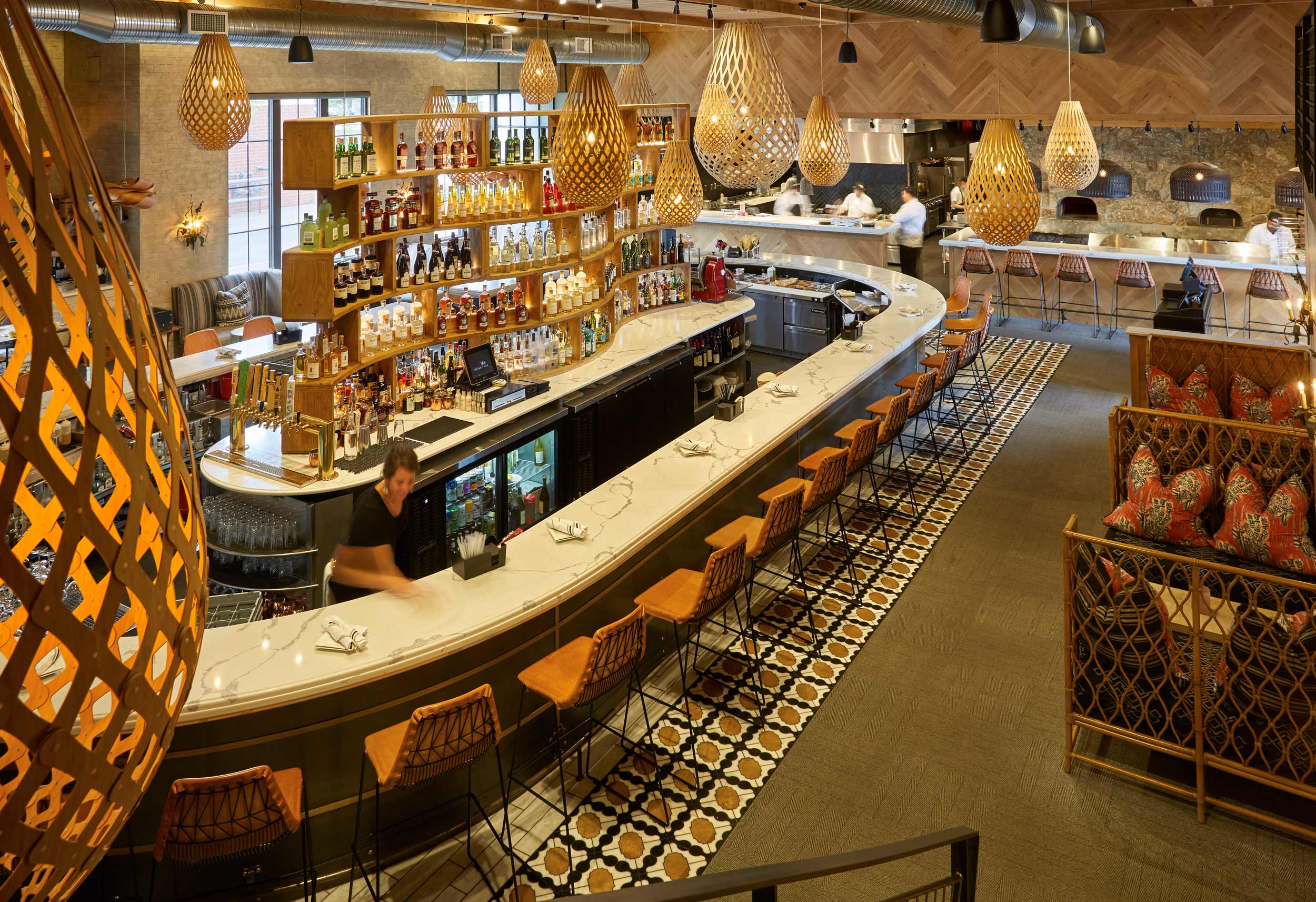 A mezzanine-view overlooks the restaurant's signature pendant lamps and expansive oval bar where the high, curving shelves hold gem-like bottles of locally distilled spirits and classic aperitifs.