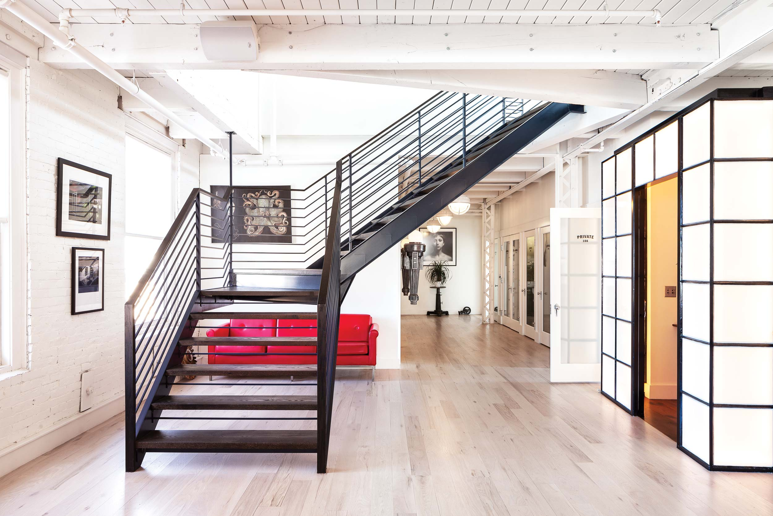 The hockey stick-shaped winder staircase, made of dark blue steel and blackened oak treads, has particularly fine connections, in lieu of posts at the staircase's flying corners.
